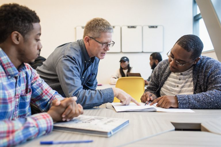 A teacher helps leans over a table to point at a young man's notebook while another young man looks on.