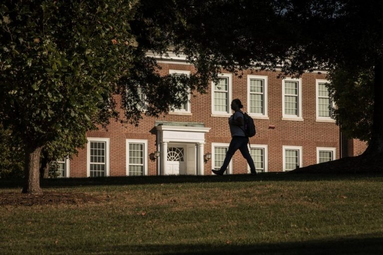 A woman with a backpack walks across a college campus.