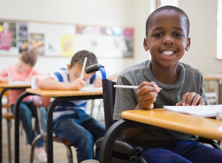 A boy in a wheelchair smiles at the camera while sitting at his classroom desk..