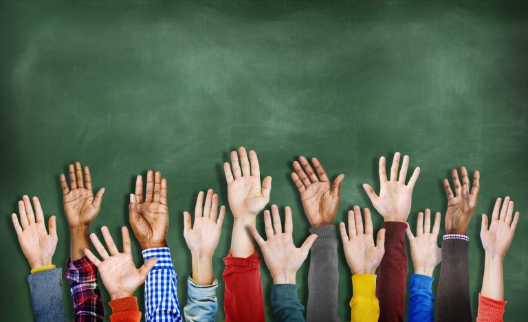 Raised hands of children in front of a chalkboard.