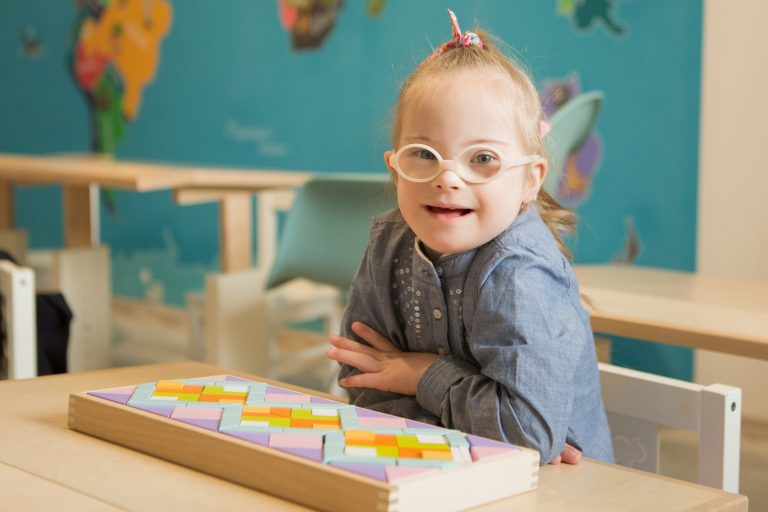 smiling girl with glasses sitting at a classroom desk. A box of pattern blocks are in front of her.