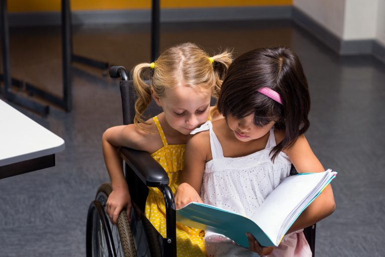 Two young girls read a book together. One girl is in a wheelchair and the other shares the seat while they look at the book.